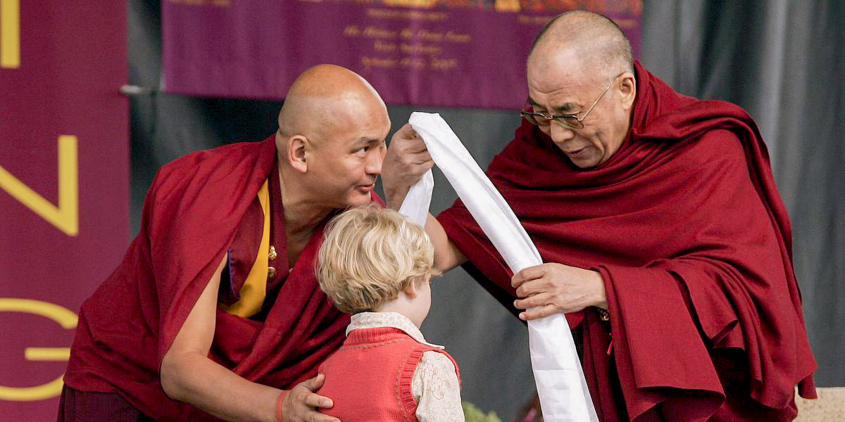 The Dalai Lama, right, places a greeting scarf on Katrina Smit, 6, of Marsing, Idaho as his emissary, Tendzin Dhonden, assists at left Monday, Sept. 12, 2005 at the Wood River High School stadium in Hailey, Idaho. Smit, who was honored for her role in providing physical therapy and other care for her disabled grandmother, was one of 18 children blessed by the Dalai Lama during a ceremony dedicated to the children of Idaho. (AP Photo/Ted S. Warren)